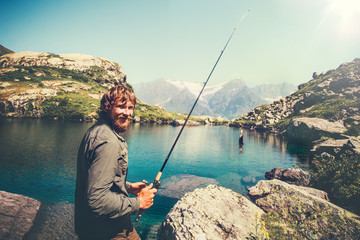Bearded Man Fisherman happy fishing with rod Lifestyle Travel survival concept lake and mountains on background