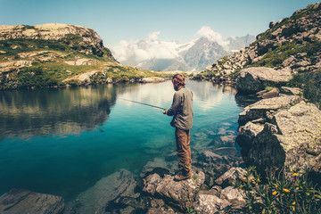 Young Man fishing on Lake with rod mountains landscape on background Travel Lifestyle concept summer vacations