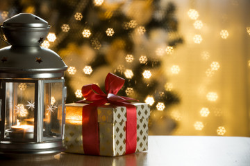 Christmas lantern with candle and gift box wrapped in golden paper and red ribbon wooden table. Beautiful decorated christmas tree with lights and balls.