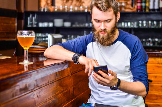 a guy sitting at the bar with a smartphone in your hands and a glass of beer