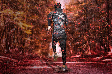 Running man in the autumnal forest at a rainy day
