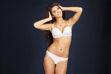 Sexy woman in white underwear on a dark wall