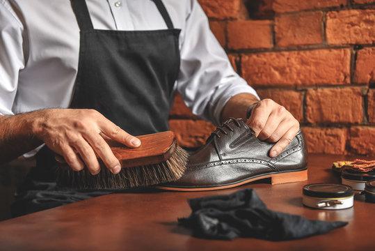 artisan in apron taking care of elegant boots