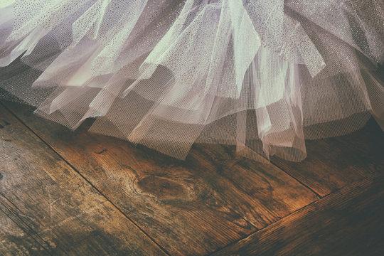 White ballet tutu on wooden floor. Retro filtered