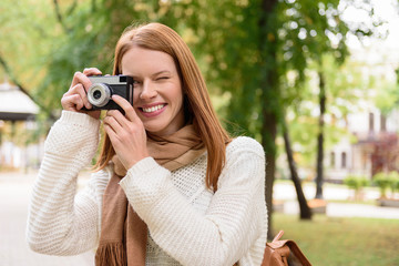 Young woman using camera in park