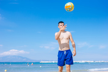 young man with volleyball playing volley on the beach