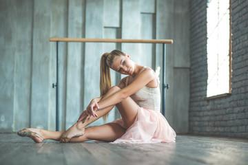 Attractive ballet dancer sitting on floor