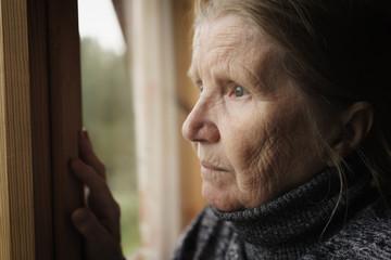 senior woman looking in a window