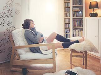 Frau mit Katze sitzt gemütlich im Wohnzimmer neben dem Fenster