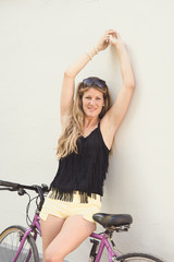 Young woman leaning on bicycle up arms