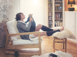 woman with a cat sitting beside the window in living room
