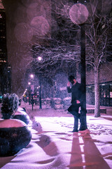 Male leaning against a pole in snowy night.