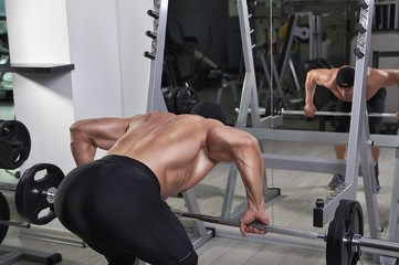 Handsome powerful athletic man doing exercise for back with barbell. Strong bodybuilder with perfect muscles.