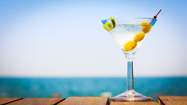 Glass of martini bianco at the wooden pier. Concept of summer va