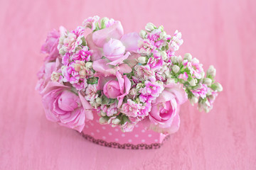 Lovely bunch of flowers .Beautiful fresh roses flowers in a box on a pink background.