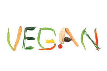 Word vegan written with vegetables, as a metaphor or concept for healthy food, living, diet, recipe. Isolated on white background