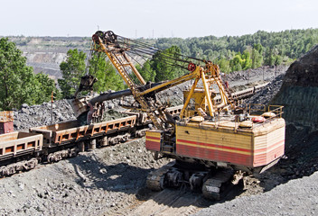 Excavator loading iron ore into goods wagon on the iron ore opencast mine