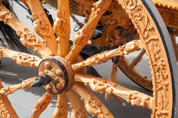 Close-up view of a wooden carved wheel of a typical sicilian cart during a folkloristic show