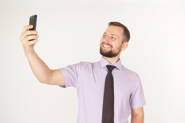 Young happy cheerful business man looking at smartphone or making selfie, isolated on white background