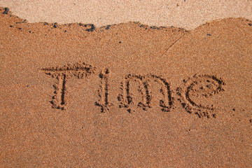 "word ""time"" written on the wet sand. wave washes off an inscription"