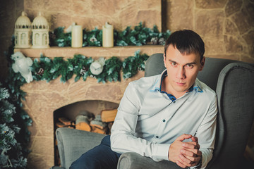 young man sitting on background of Christmas interior
