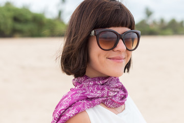 Beauty portrait of sexy brunette woman on the beach with colorful silk scarf and sunglasses. Cruise summer fashion. Bali, Indonesia.
