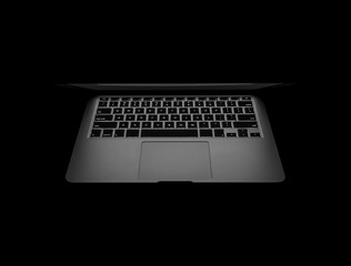 New computer laptop showing keyboard backlight and touchpad in the dark background.