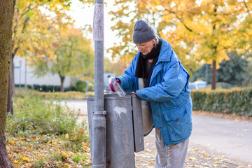 Indigent senior woman scrounging through a bin
