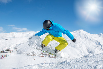 Young snowboarder in protective gear jumping
