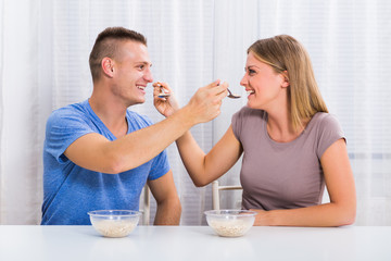 Young happy couple enjoys feeding each other with breakfast.
