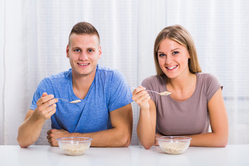 Young happy couple enjoys having breakfast together.