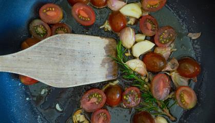 Tomanten mit Knoblauch und Kräutern in einer Pfanne - Close Up