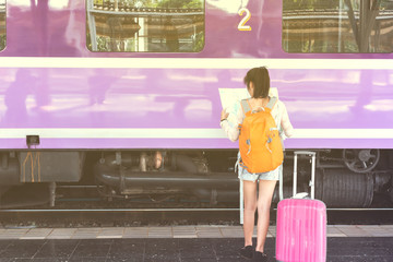 Orange helmet and backpack at the train station with tourists. Travel ideas