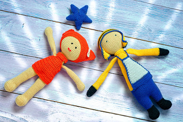 the concept of a happy couple - knitted toys girl and boy lay un