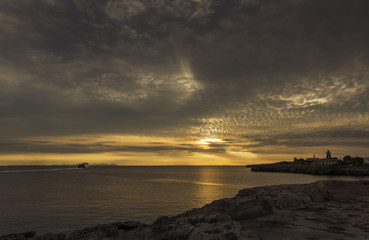 Amazing sunset over the sea with a ship and  lighthouse in foreground. Menorca, Spain