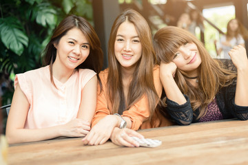 Three beautiful happy Asian girl smile and laugh together.Image with sunlight filter.