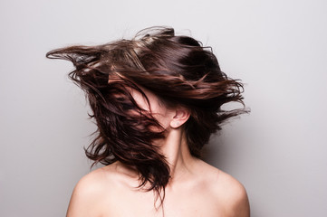 Stop action photograph of a beautiful woman with brunette hair creating motion with her hair.