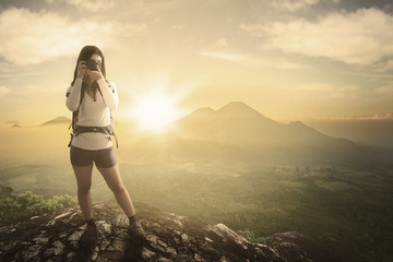Woman standing on the rock with a camera