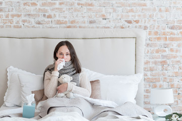 Unhappy sick woman resting on the bed