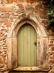 Alte gotische Tür in einer Bruchstein-Mauer