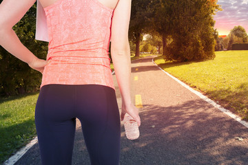 Running woman holding bottle of water, ready to start.