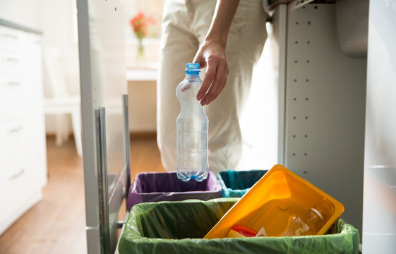 Woman putting empty plastic bottle in recycling bin in the kitchen. Person in the house kitchen separating waste. Different trash can with colorful garbage bags.