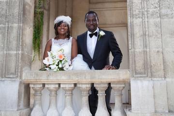 Multi-ethnic beautiful bride and groom hugging outdoor,