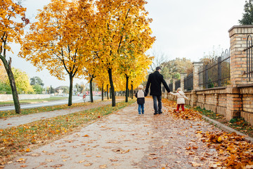Father with children in autumn street
