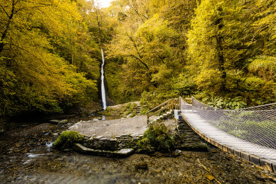 Suspension bridge and waterfall in autumn forest