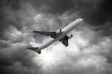 Airplane above Dark storm sky and shining Sun