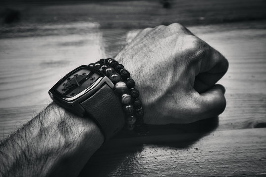 Men's brutal hand of the clock and decorative bracelets. black and white photography