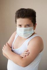fat boy wearing shirt and surgical mask looking at camera
