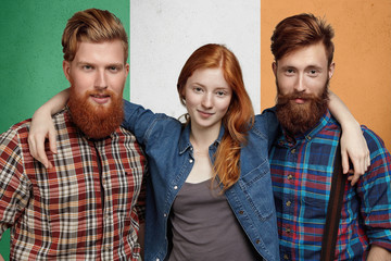 People, friendship and patriotism concept: group of happy teenage friends posing together against flag of Ireland. Portrait of cute redhead student girl hugging two young bearded men in shirts