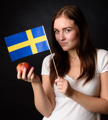 Girl with Swedish flag holding an apple (ingrid marie) isolated on black background